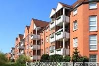 Rotes Mehrfamilienhaus mit Balkonen
