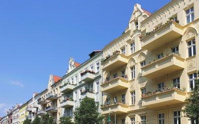 Investieren gelbes Wohnungshaus mit Balkonen